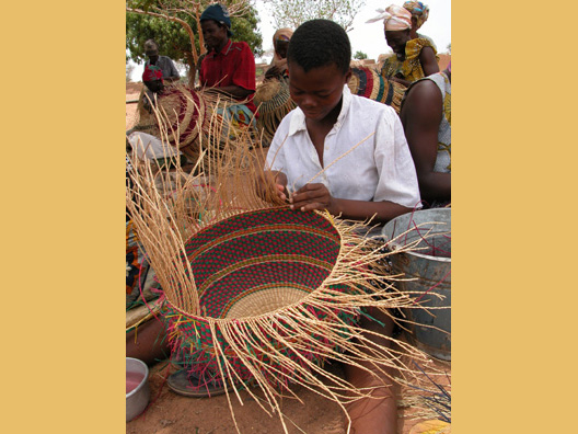 Artist weaving the African Market Baskets